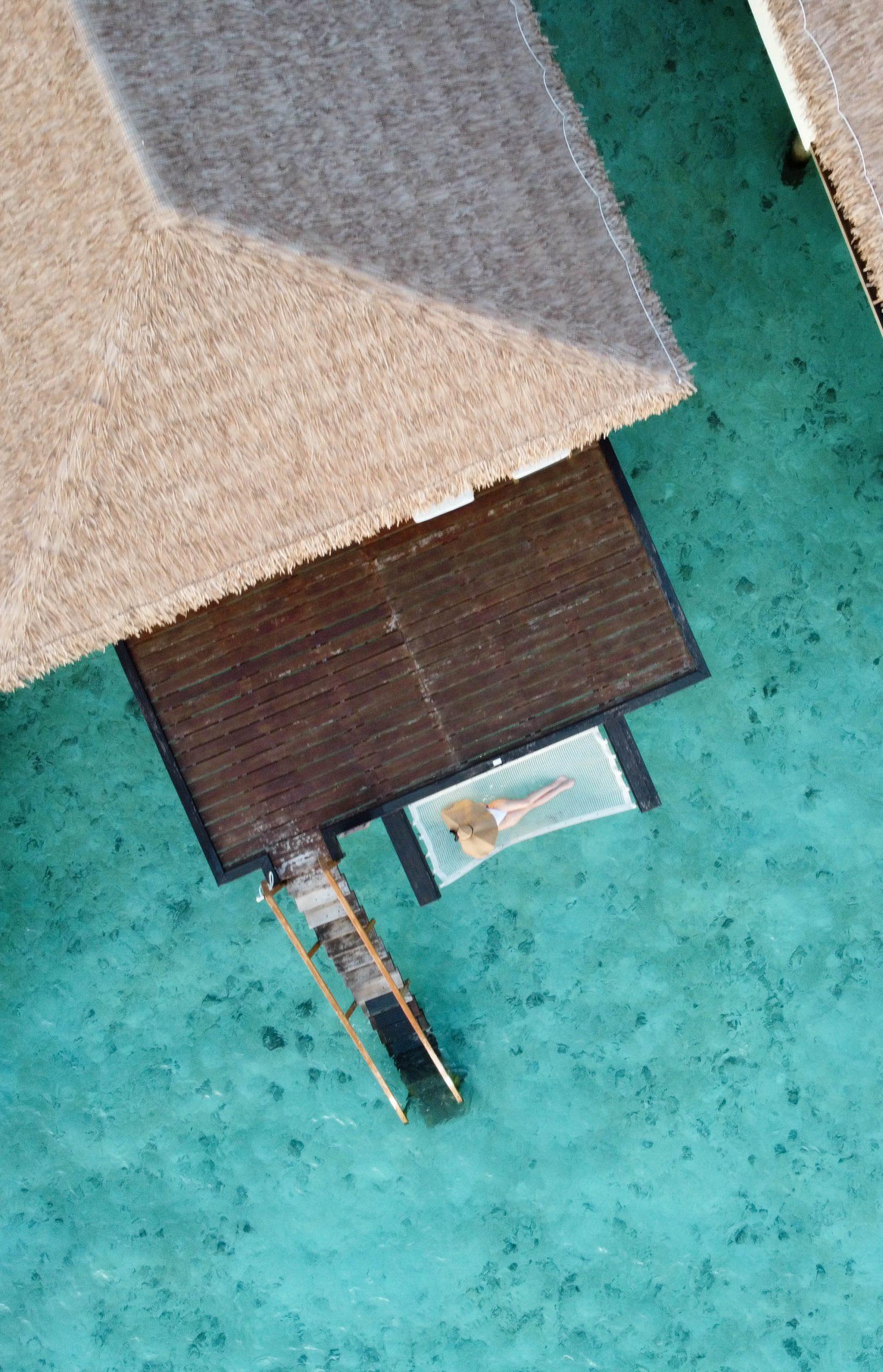 cinnamon velifushi overwater villa bungalow dron dji mavic mini clear turqoise blue water asia oversized floppy sun hat woman laying down