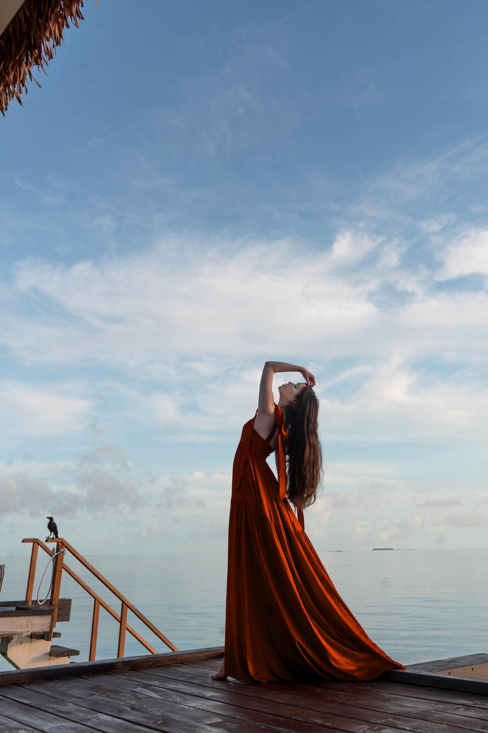 overwater villa maldives asia long brown hair brunette maxi dress with a train perrin and co anne silk dress orangess