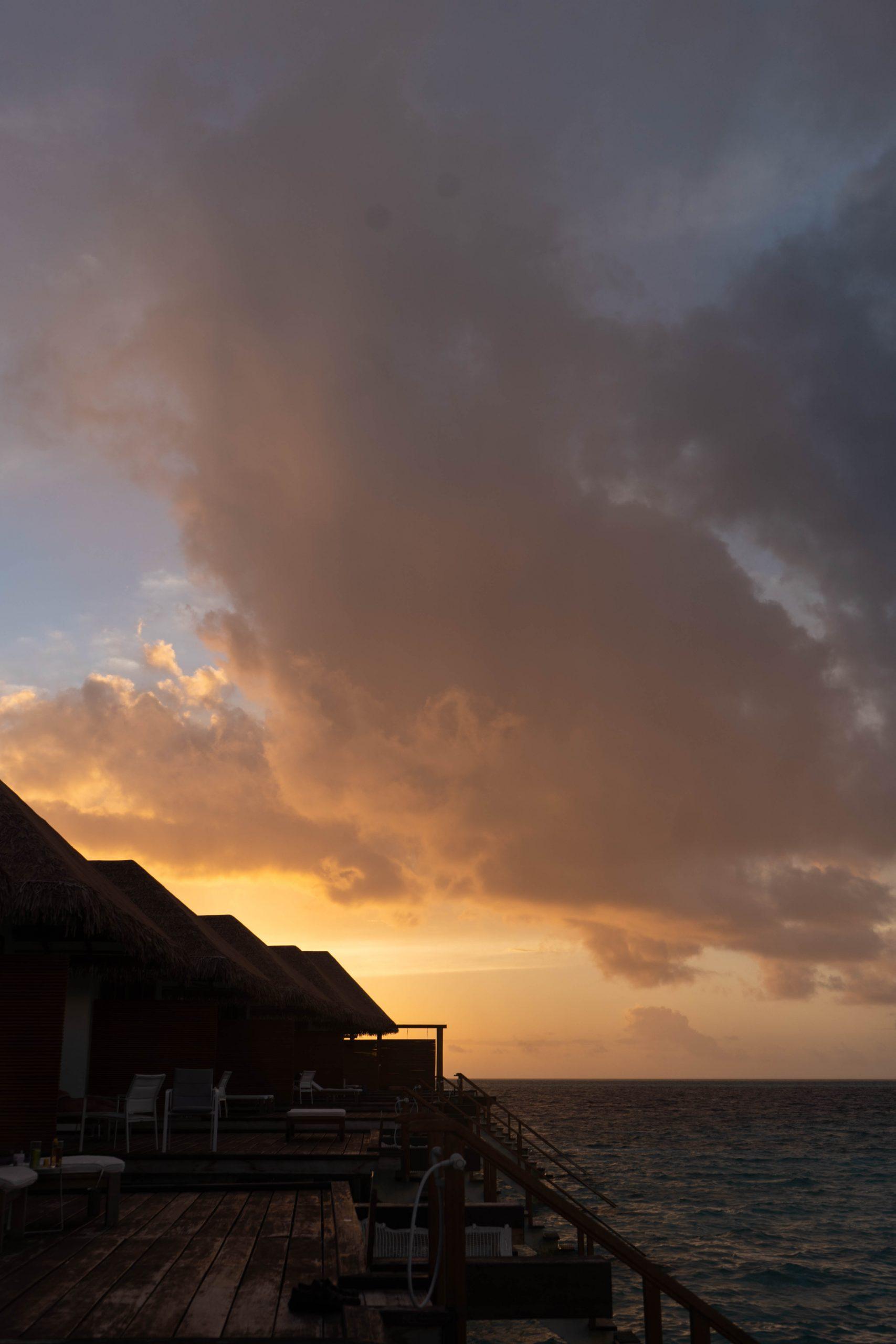 sunset overwater villa cinnamon velifushi maldives south asia indian ocean big cloud orange sky