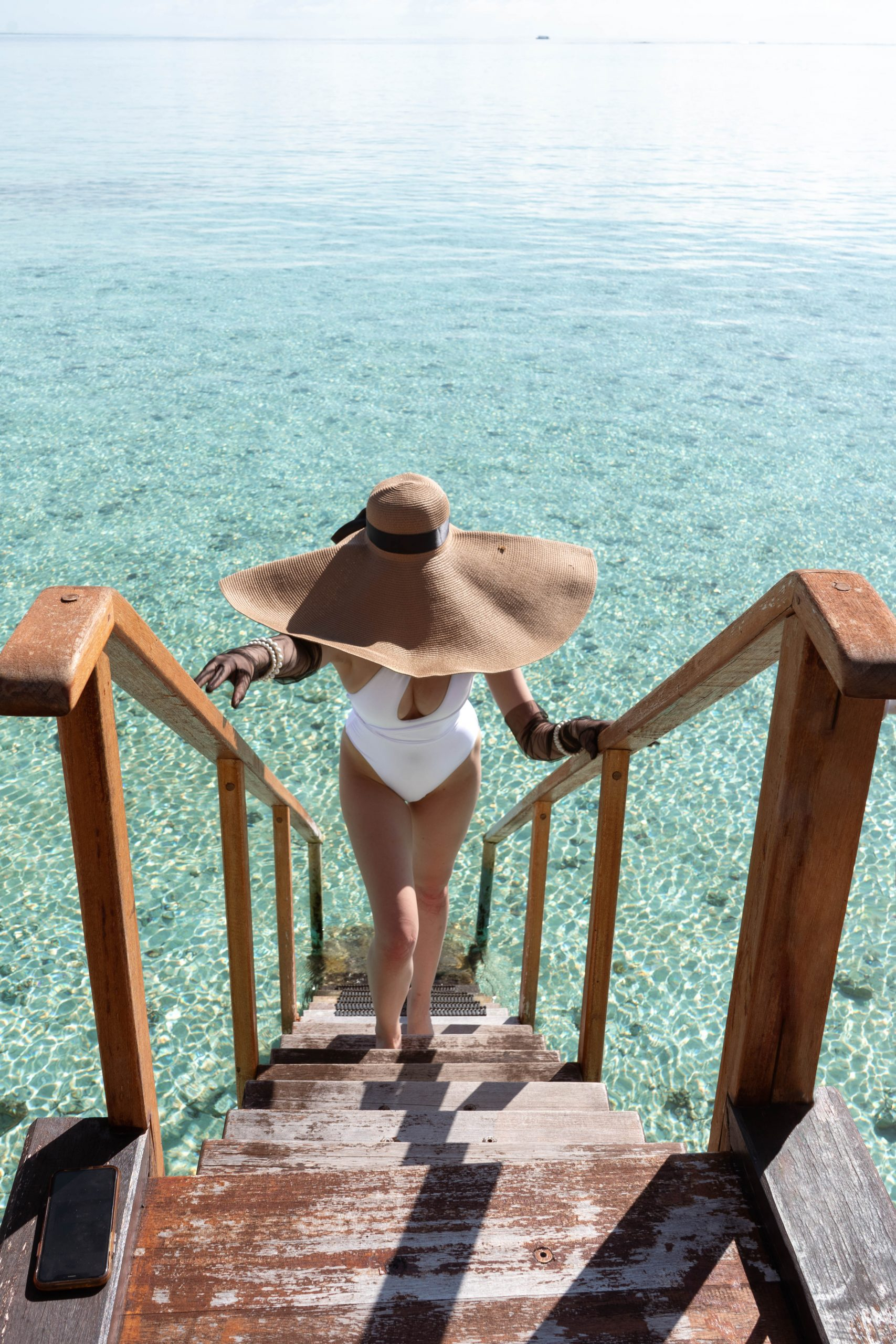 oversize floppy straw sun hat one shoulder white one piece swimsuit black tulle gloves pearl bracelets woman walking up staircase indian ocean clear turquoise blue water maldives