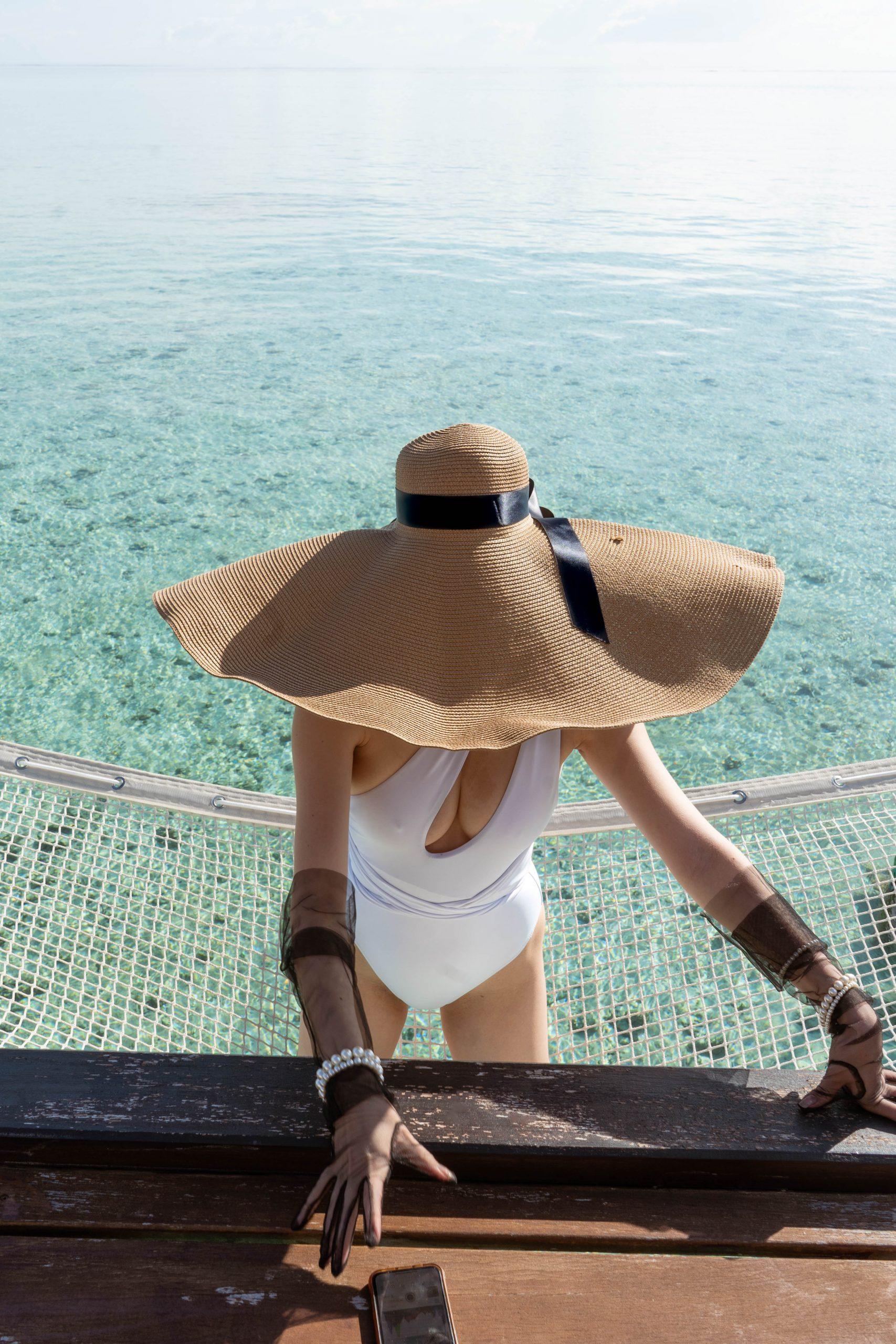 oversized straw sun hat floppy black ribbon inexpensive white one piece swimsuit one shoulder cutout black tulle mesh glove pearl bracelet maldives indian ocean hammock net