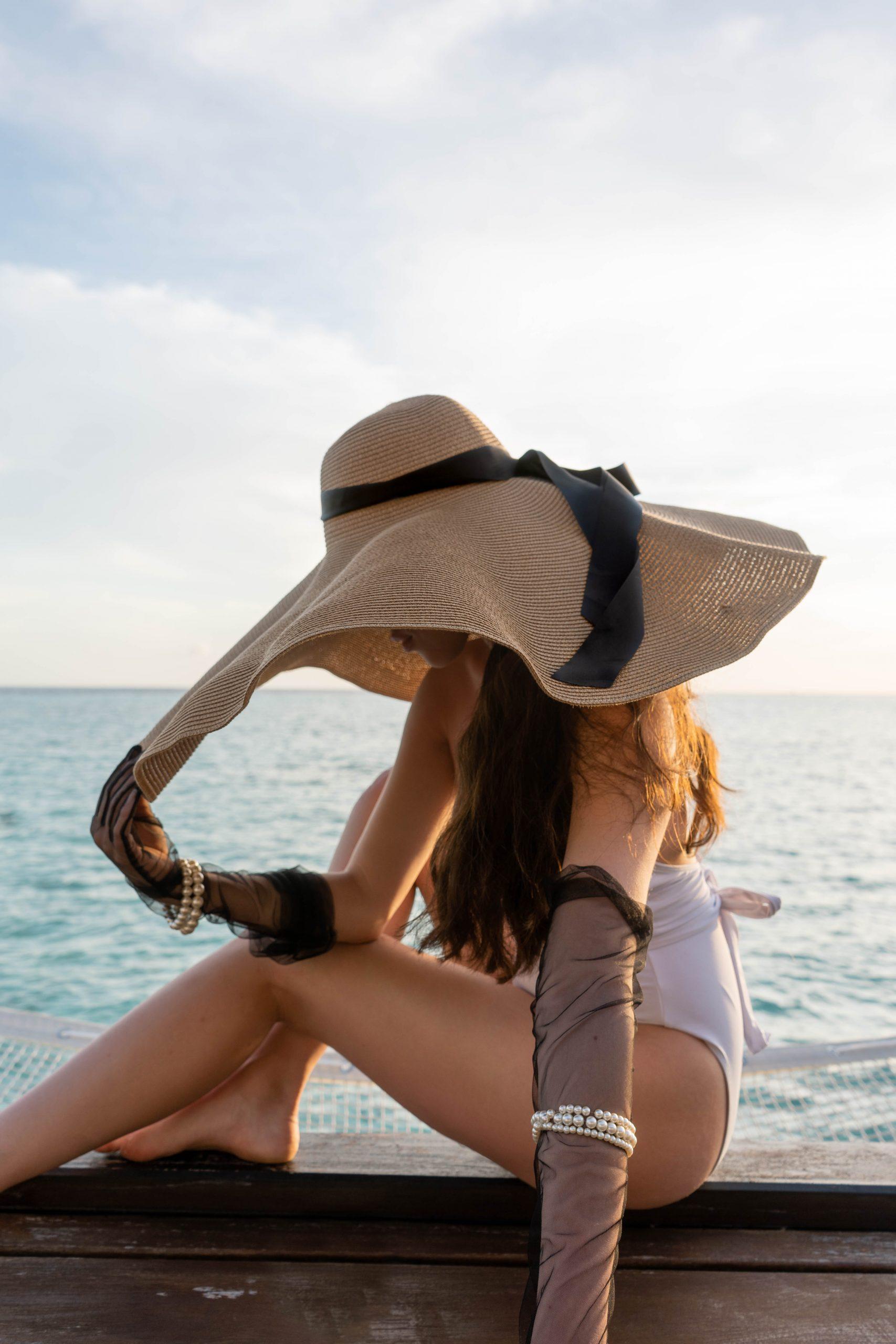 oversized straw sun hat floppy black ribbon inexpensive white one piece swimsuit black tulle mesh glove pearl bracelet maldives indian ocean eva phan