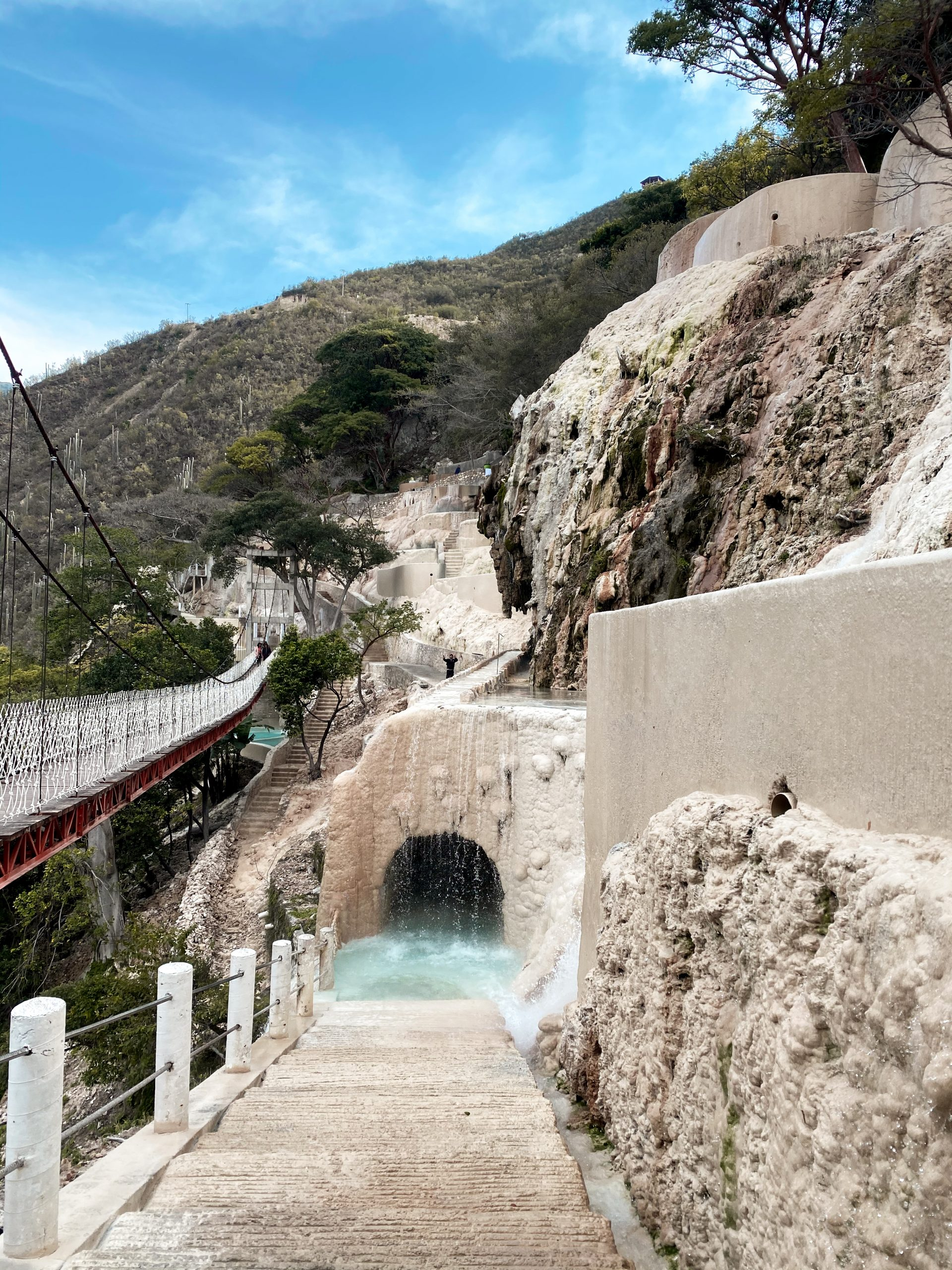 tunnel carved white stone thermal pool cliff side canyon natural hot springs grutas tolantongo hidalgo mexico water park suspension bridge mezquital valley