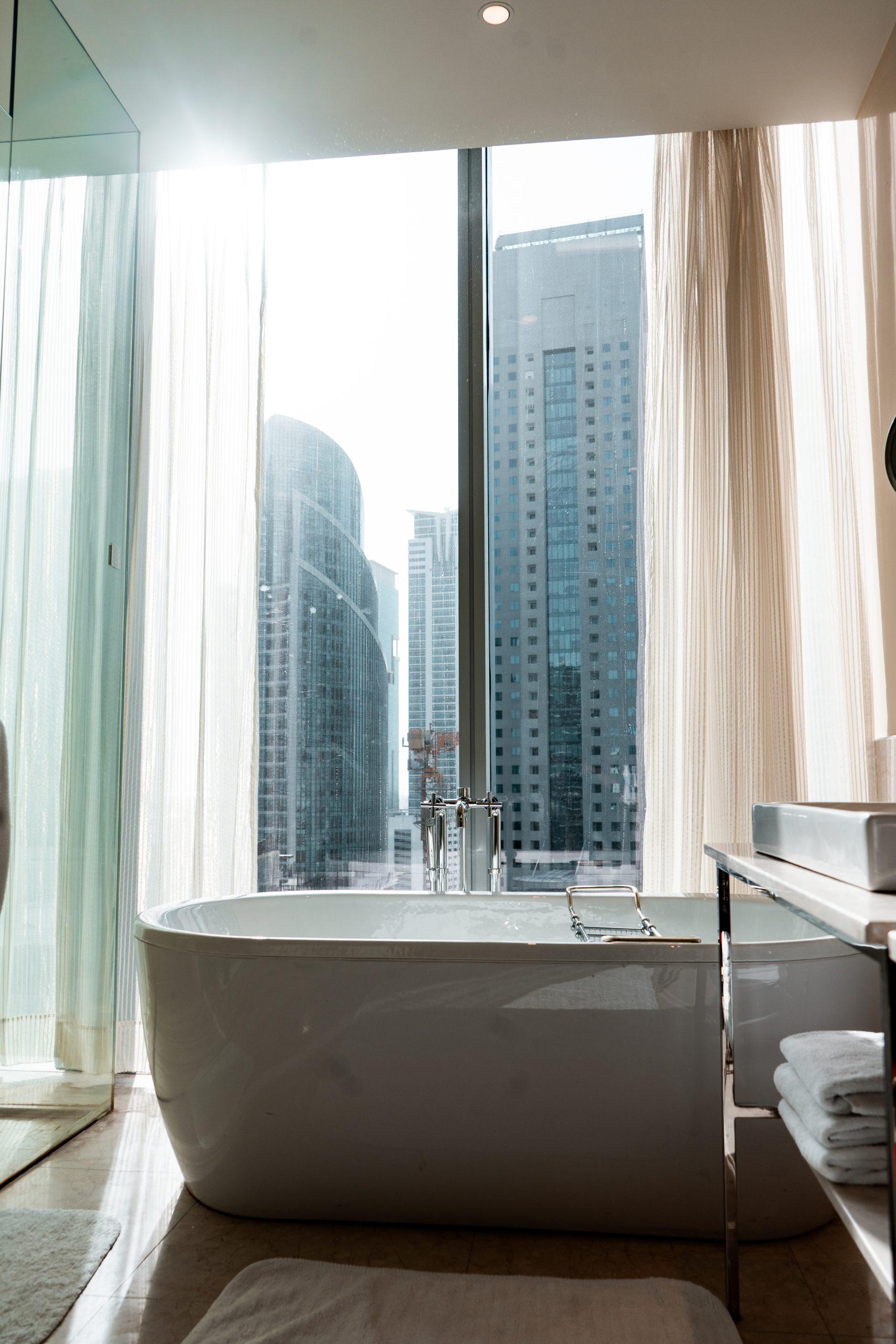 the oberoi dubai king room bathroom white porcelain standalone bathtub city view luxury hotel room bathroom